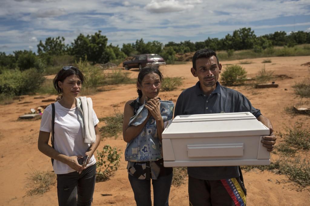 Roberto Parra carries the remains of his son Matias Alejandro alongside his wife Maria Isabel Parra and daughter Alejandra Parra at San Sebastian muni...