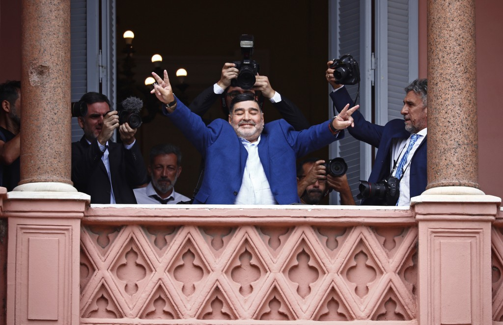 Former soccer great Diego Maradona flashes victory signs to fans below at the Casa Rosada government house after meeting with Argentine President Albe...