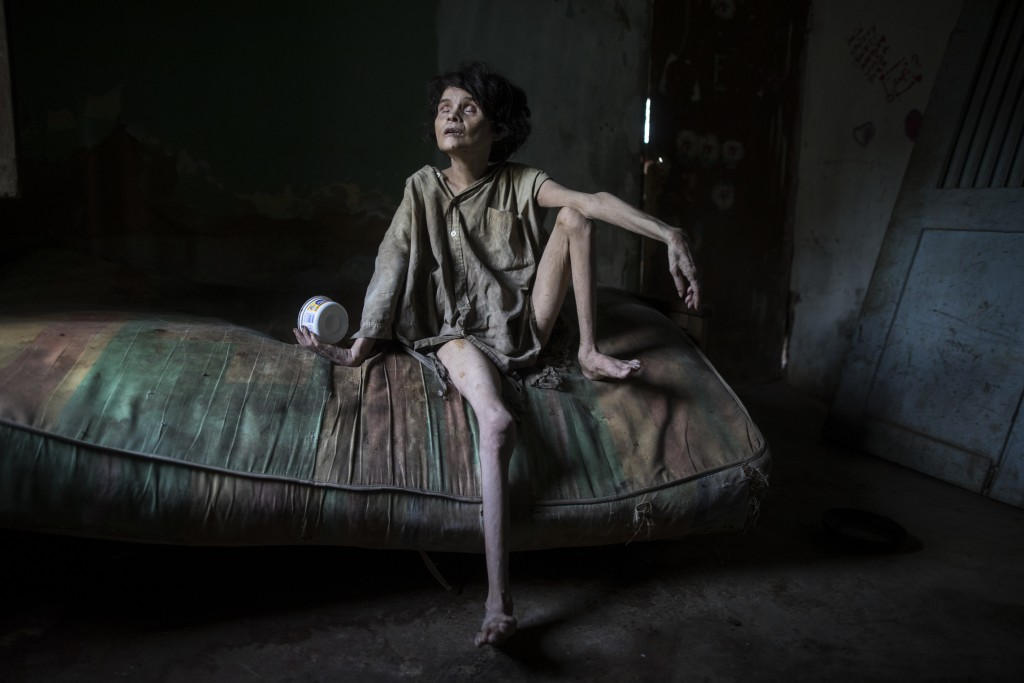 In this Nov. 28, 2019 photo published on Dec. 27, Zaida Bravo, who suffers Parkinson's disease and is malnourished, waits for dinner on her dirty matt...