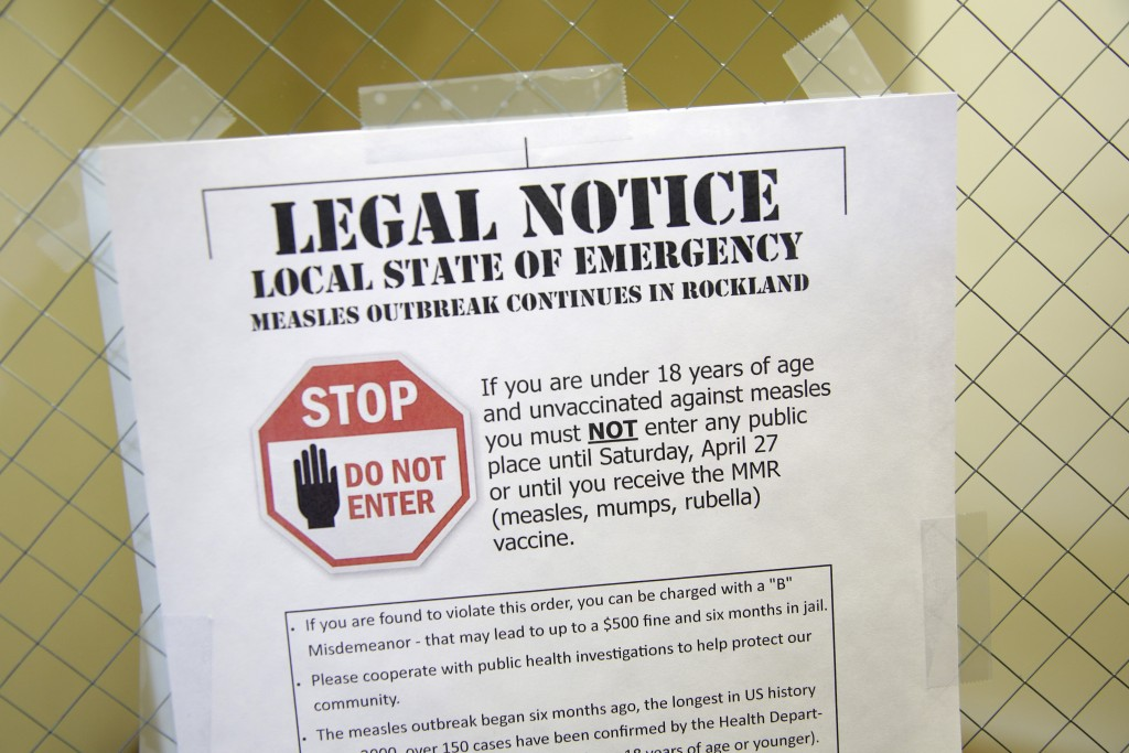 FILE - In this Wednesday, March 27, 2019 file photo, a sign at the Rockland County Health Department in Pomona, N.Y., explains the local state of emer...