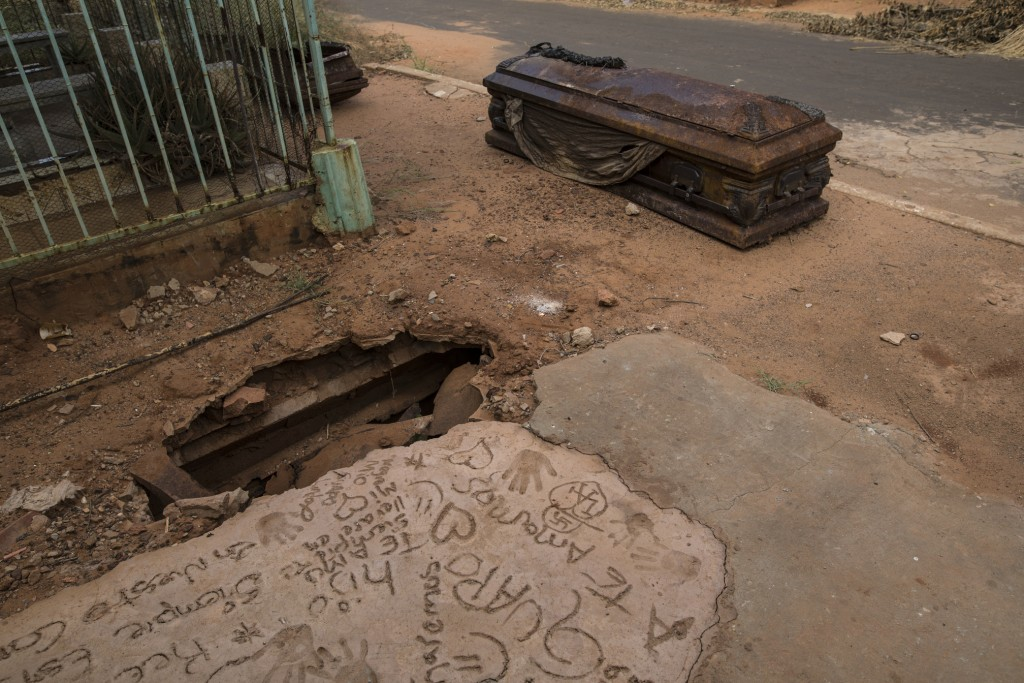 """An oxidized coffin lies next to a grave that was dug up by thieves at """"Corazon de Jesus"""" cemetery, or Heart of Jesus cemetery, in Maracaibo, Venezuela..."""