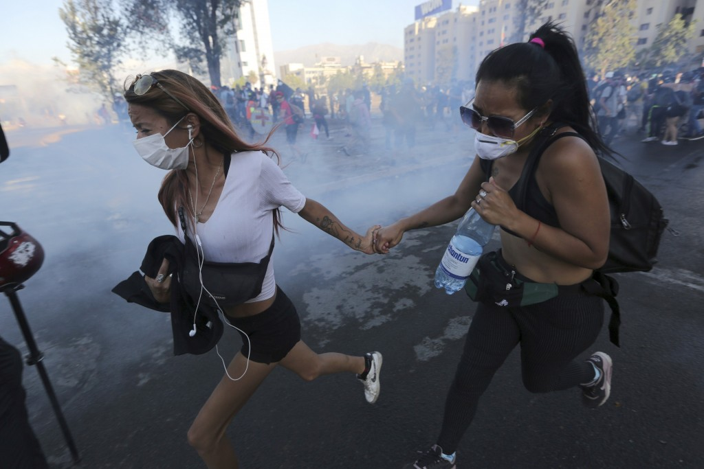 Anti-government demonstrators run away from a cloud of teargas during clashes with the police in Santiago, Chile, Friday, December 20, 2019. Chile is ...