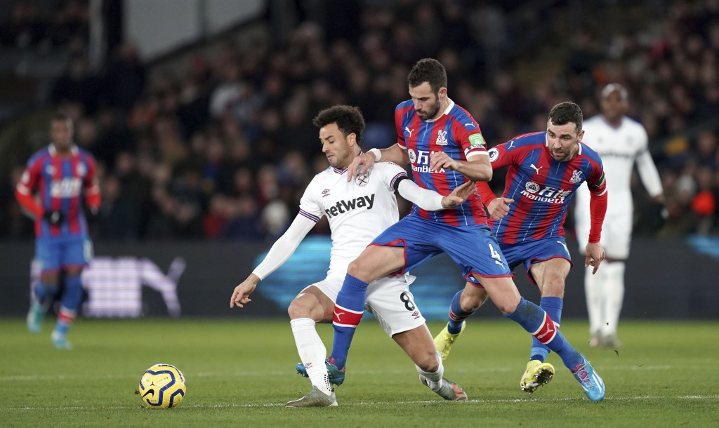 Crystal Palace's Luka Milivojevic, center, and West Ham United's Felipe Anderson battle for the ball during their English Premier League soccer match ...