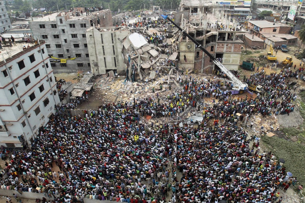 FILE - In this April 25, 2013, file photo, Bangladeshi people gather as rescuers search for survivors and victims after the Rana Plaza building collap...