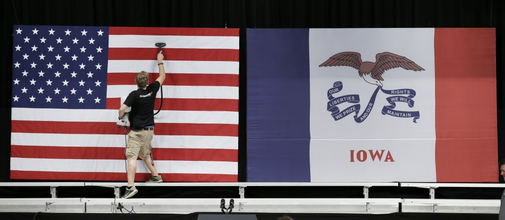 FILE - In this Sept. 14, 2015, file photo, a worker steams wrinkles out of a US flag before the arrival of President Barack Obama at a town hall meeti...