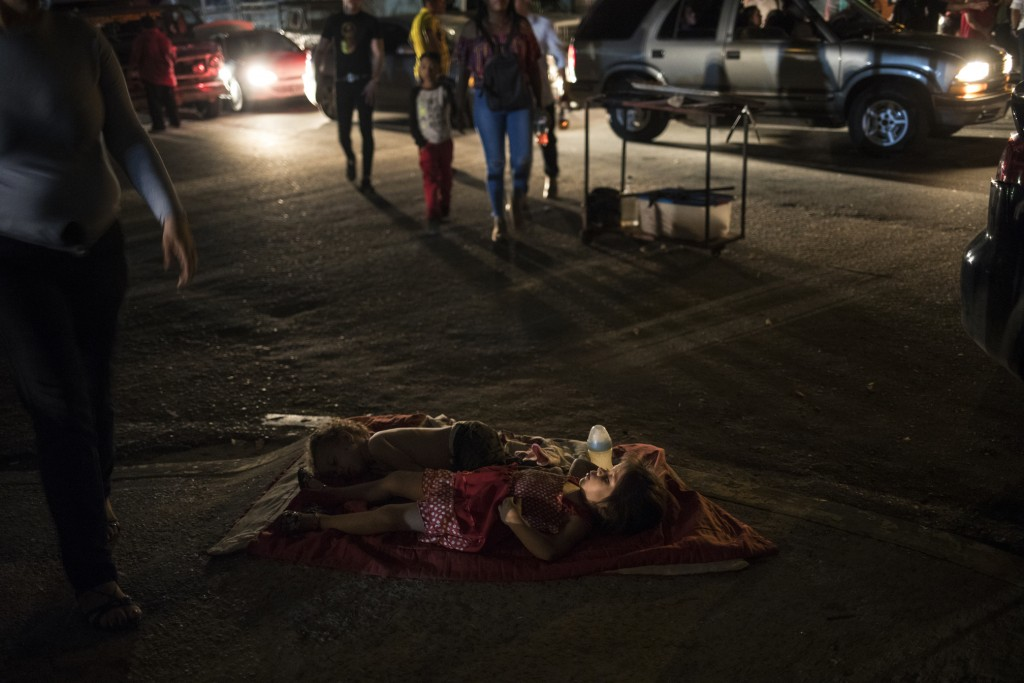 Children sleep in the street near their mother's food stand where she sells food to people attending an event marking the feast day of Our Lady of Chi...