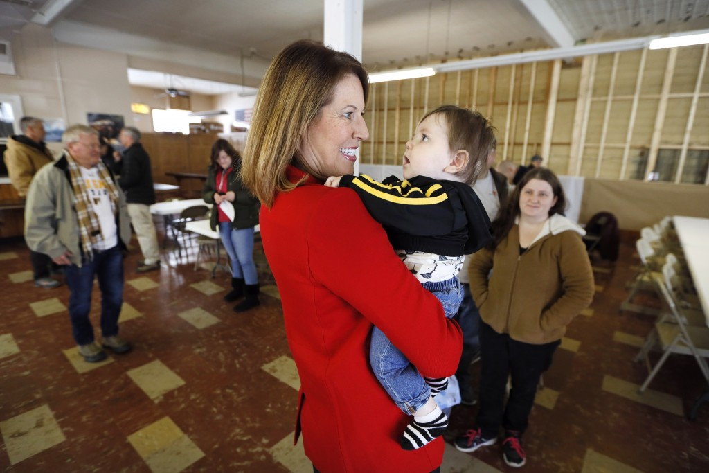 In this Nov. 11, 2019, photo, U.S. Rep. Cindy Axne, D-Iowa, holds a baby after speaking to local residents at the American Legion Post 184 in Winterse...