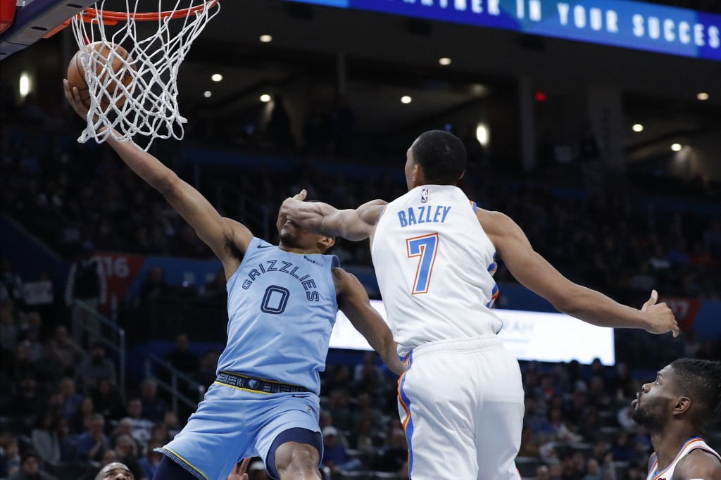 Memphis Grizzlies guard De'Anthony Melton (0) is hit and fouled by Oklahoma City Thunder forward Darius Bazley (7) on his way to the basket during the...