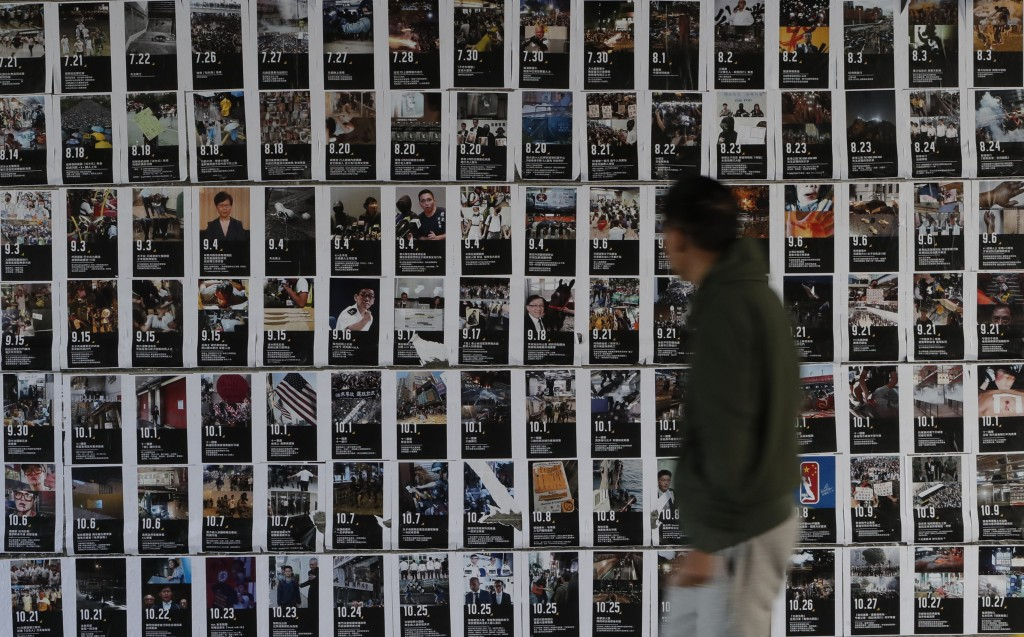 A man walks past a wall of posters featuring demonstration scenes in Hong Kong, Friday, Dec. 27, 2019. Hong Kong's demonstrations erupted in June over...