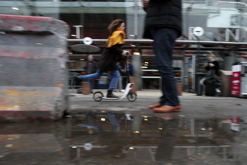 A woman rides a scooter at Gare Montparnasse station in Paris, Friday, Dec. 27, 2019. French union activists are disrupting two of the country's eight...