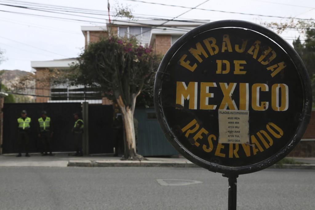 A sign announces Mexico's embassy where Bolivian police stand guard in La Paz, Bolivia, Thursday, Dec. 26, 2019. Mexico's Foreign Relations Secretary ...