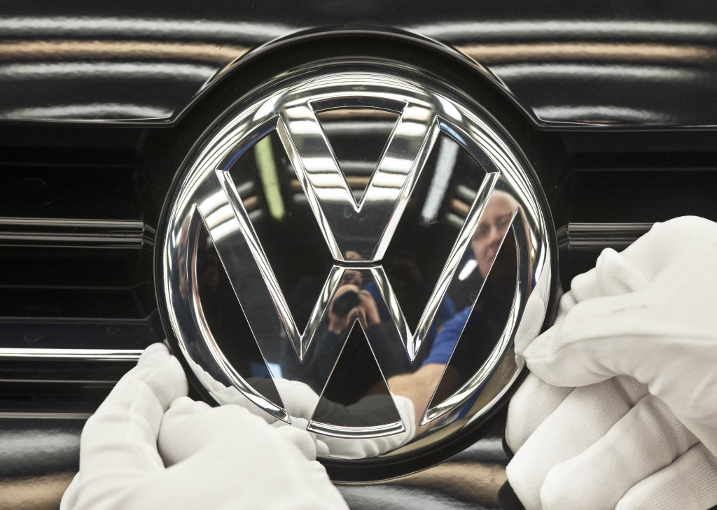 FILE - In this Nov. 9, 2012 file picture a worker fixes a sign at a Volkswagen Golf car during a press tour in Zwickau, central Germany. Automaker Vol...