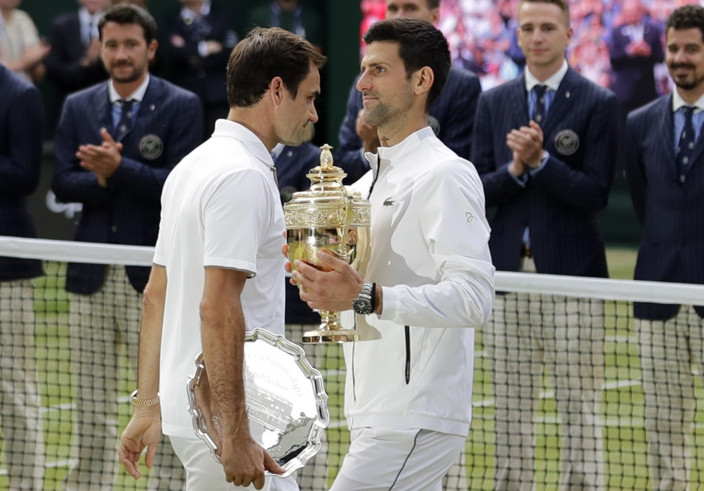 FILE - In this July 14, 2019, file photo, second placed Switzerland's Roger Federer, left, walks past winner Novak Djokovic, of Serbia, during trophy ...