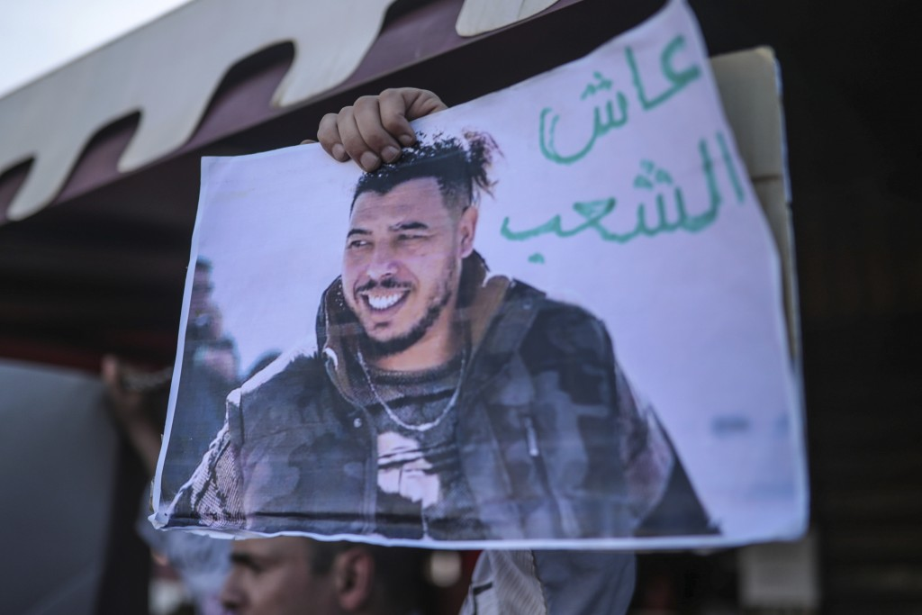 FILE - In this Monday, Nov. 25, 2019, file photo, protesters carry a photo of Moroccan rapper Gnawi outside a court where he was on trial on charges o...