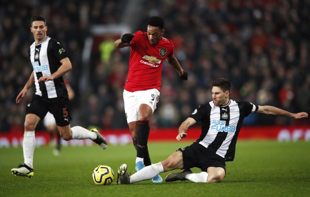 Manchester United's Anthony Martial, center, and Newcastle United's Federico Fernandez battle for the ball  during their English Premier League soccer...