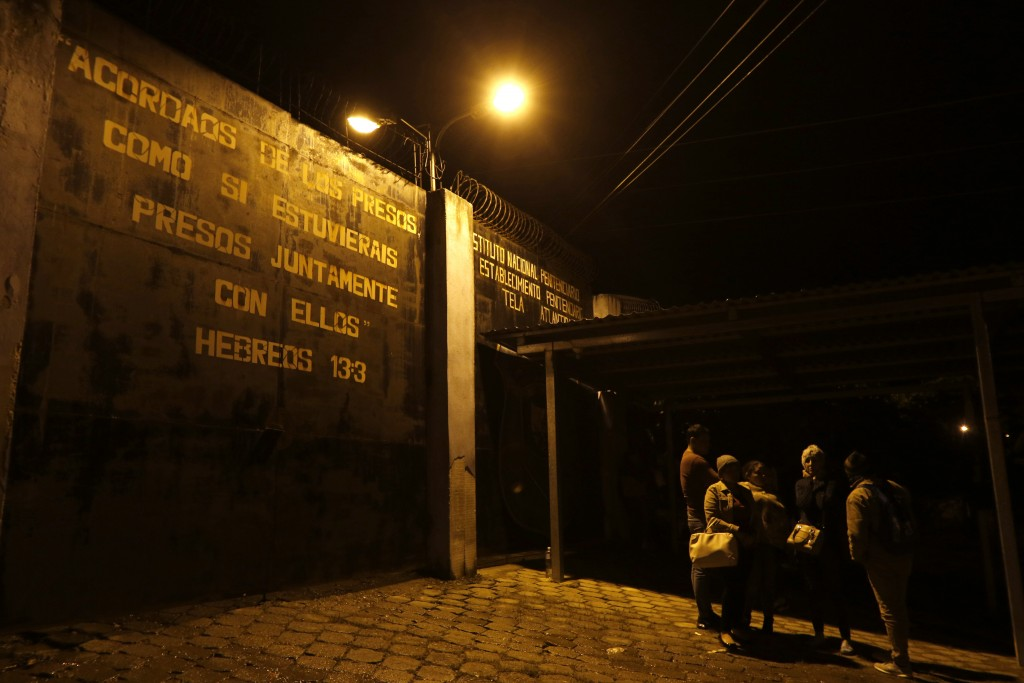 Family members wait outside the prison gate for news from their imprisoned relatives, outside the Tela prison where at least 18 inmates were killed on...