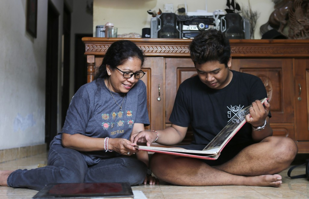 Ni Luh Erniati sits with her son, Made, going through family photo albums which show her late husband and his late father, Gede Badrawan, in Bali, Ind...