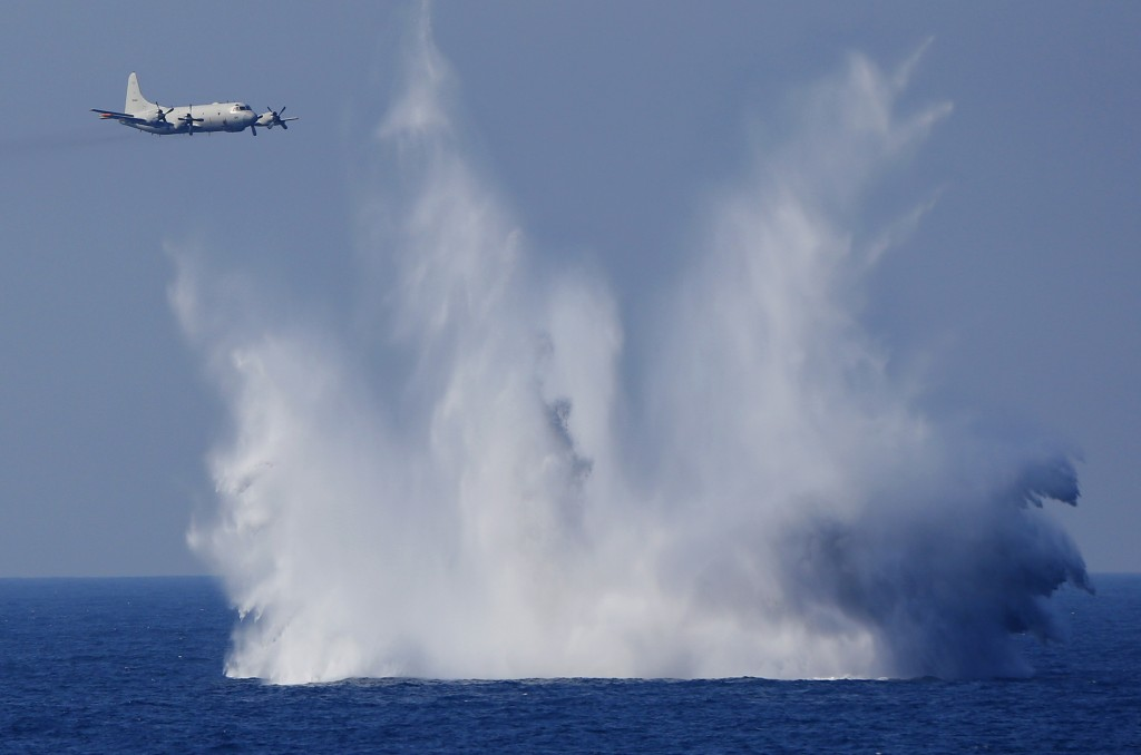 FILE - In this Oct. 18, 2015, file photo, a P-3C anti-submarine patrol plane of the Japan Maritime Self-Defense Force (JMSDF) flies after dropping ant...