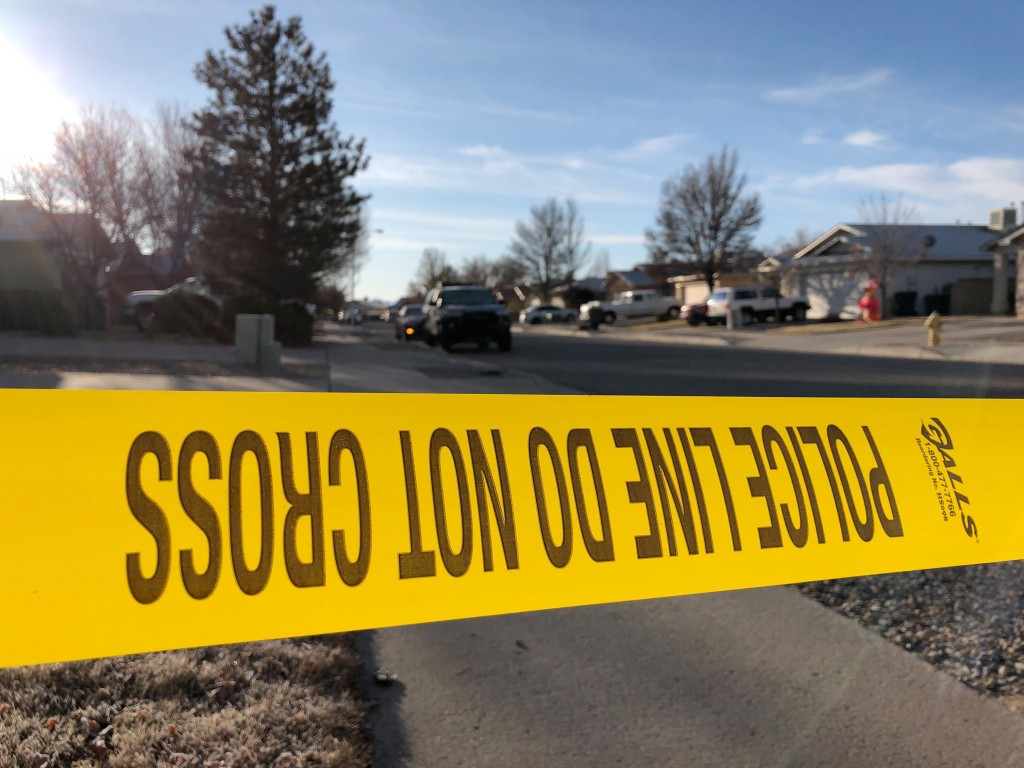 Police have a residential street cordoned off as detectives investigate the deaths of four people found Christmas Day inside a home in Rio Rancho, N.M...