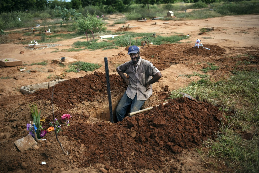 Cemetery worker Denny Pereyra rests momentarily while digging graves for children in an area of the municipal cemetery reserved for common graves in M...