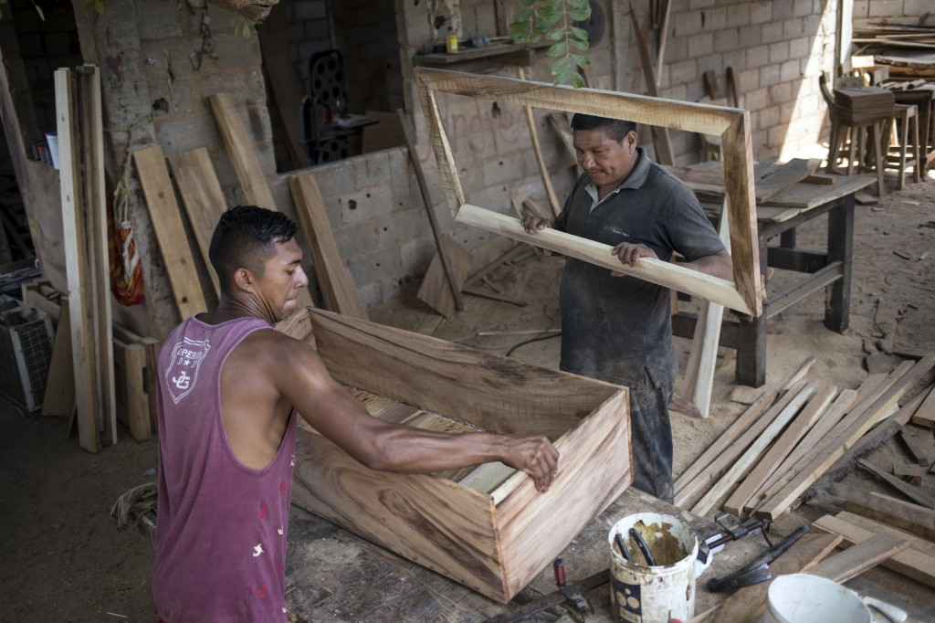 Sergio Morales, right, and Joelvis Cantillo, build a simple coffin at their furniture workshop in Maracaibo, Venezuela, Nov. 20, 2019. Two years ago t...