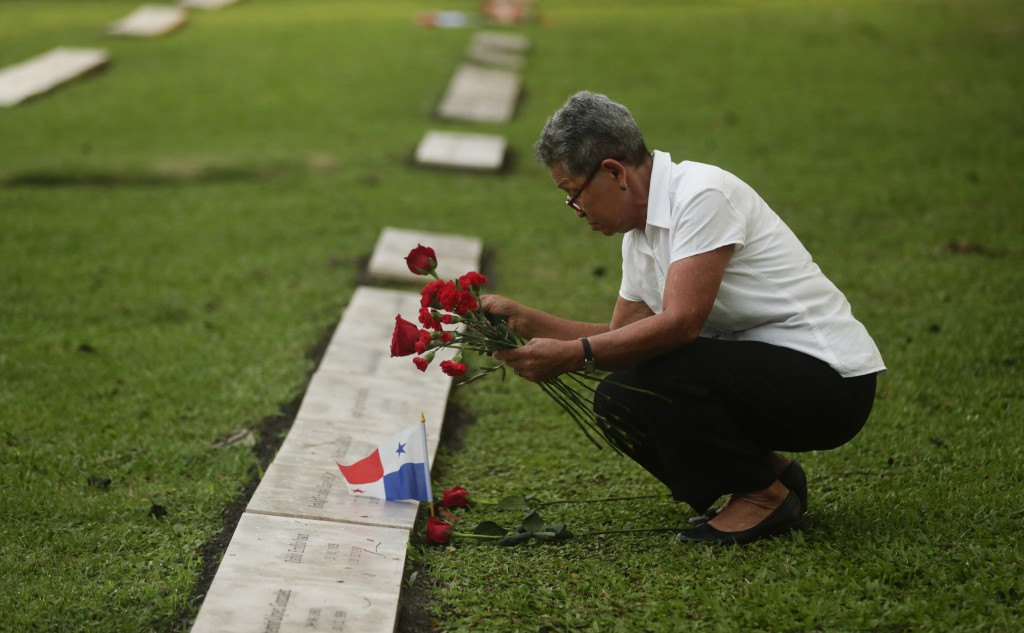 A woman places flowers on the grave of a person who died during the 1989 U.S. military invasion that ousted Panamanian strongman Manuel Noriega, on th...