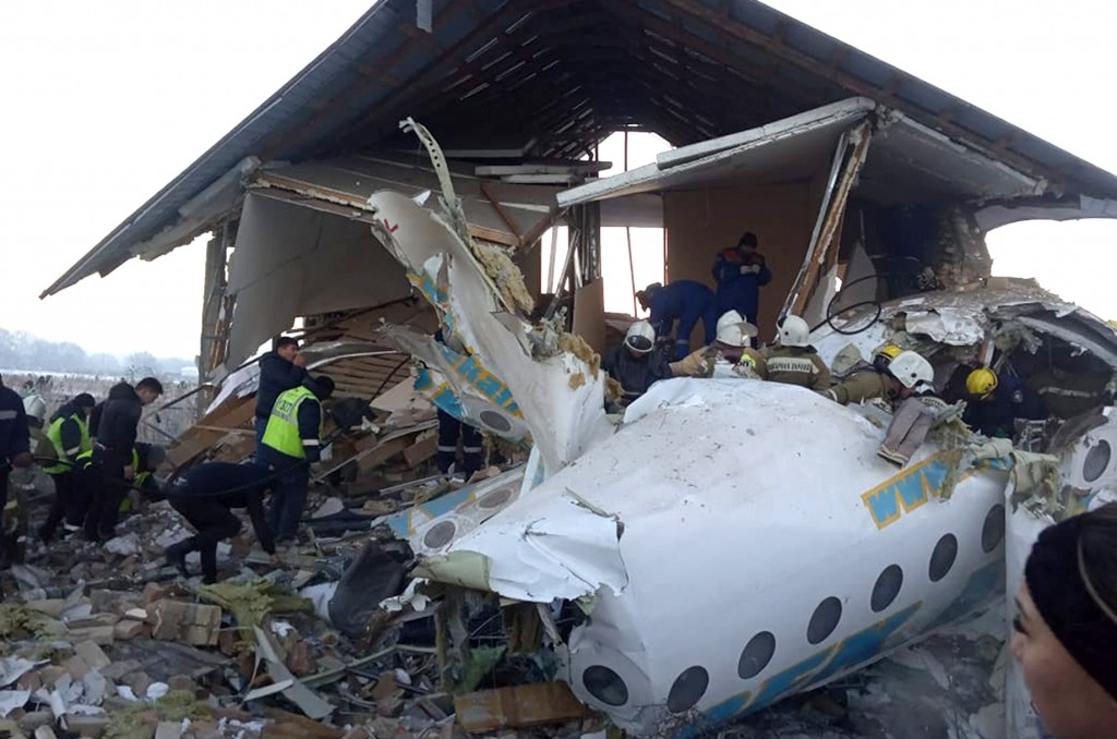 In this handout photo provided by the Emergency Situations Ministry of the Republic of Kazakhstan, police and rescuers work on the side of a plane cra...