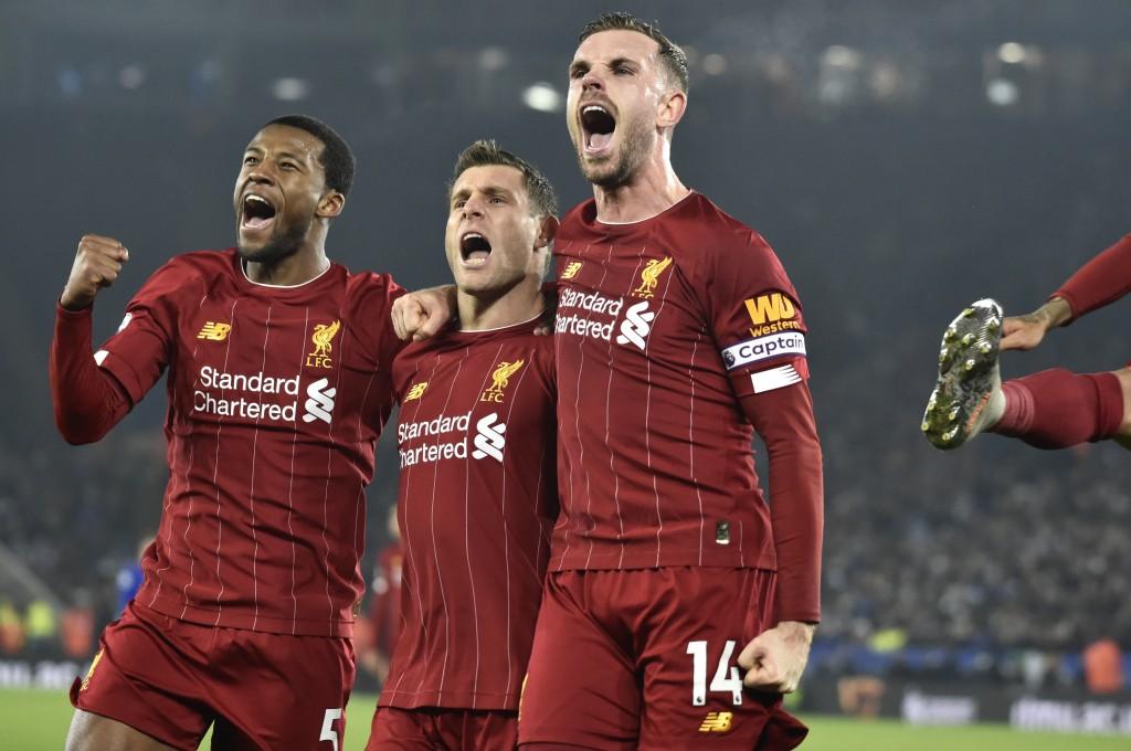 Liverpool's James Milner, second left, celebrates with his teammate Liverpool's Georginio Wijnaldum, left, and Liverpool's Jordan Henderson after scor...
