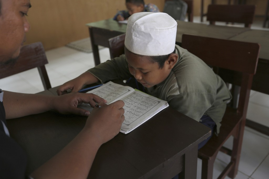 A Muslim student reads the Quran at an Islamic boarding school in Tenggulun, East Java, Indonesia, on Saturday, April 27, 2019. The school is part of ...