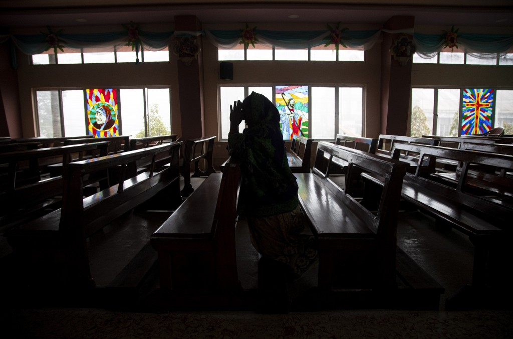 In this Wednesday, Dec. 25, 2019, file photo, an Indian Christian woman offer prayers at a church on Christmas in Gauhati, India. Though the Hindus an...