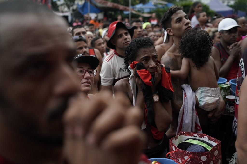 Fans of Brazil's Flamengo soccer team watch a live broadcast of the FIFA Club World Cup final soccer match against England's Liverpool, at the Rocinha...