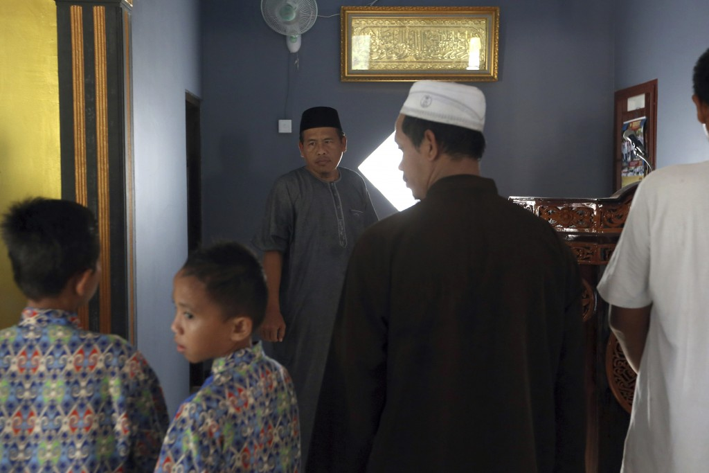 Ali Fauzi, center, prepares to pray at a mosque in Tenggulun, East Java, Indonesia, on Saturday, April 27, 2019. Three of Fauzi's brothers helped orch...