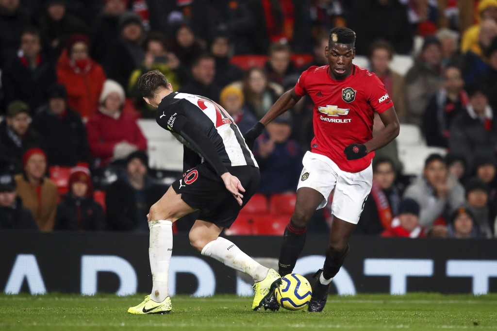 Manchester United's Paul Pogba, right, and Newcastle United's Florian Lejeune battle for the ball during their English Premier League soccer match at ...