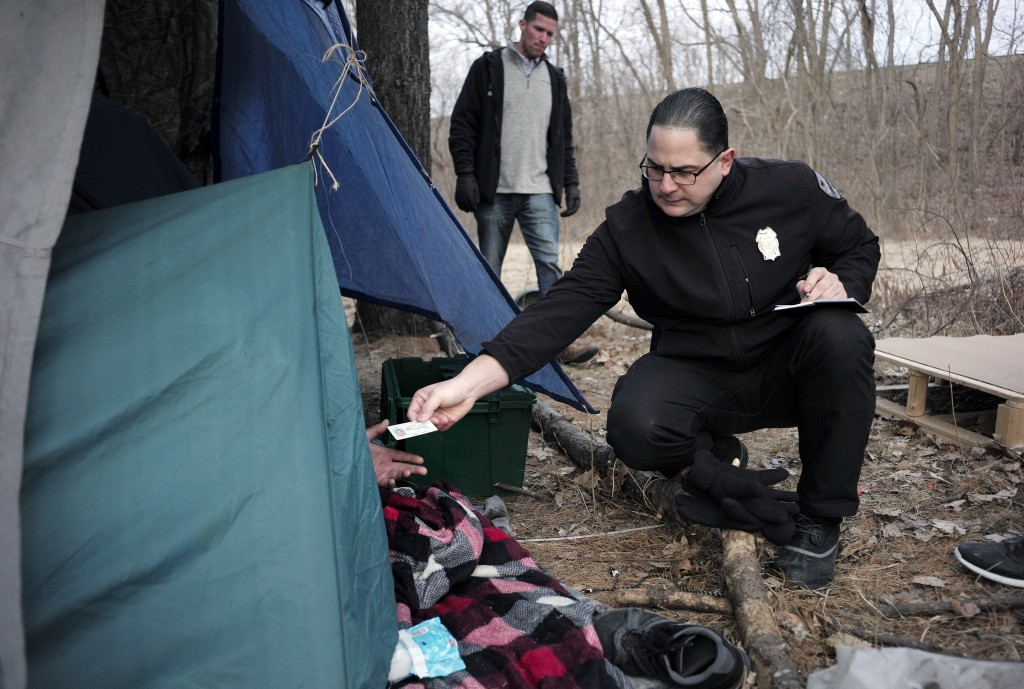 FILE - In this Tuesday, Feb. 12, 2019 file photo Worcester Police officer Angel Rivera, right, returns a license to an unidentified man as Rivera asks...