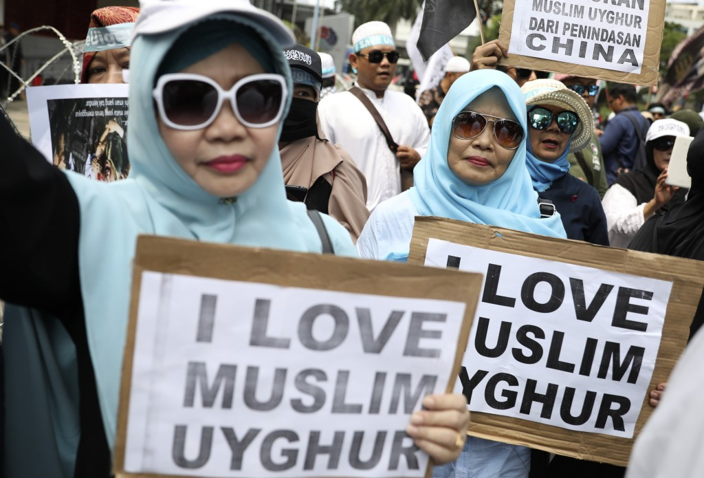 Muslim women hold posters during a rally outside the Chinese Embassy in Jakarta, Indonesia, Friday, Dec. 27, 2019. Over a thousand Muslims staged the ...