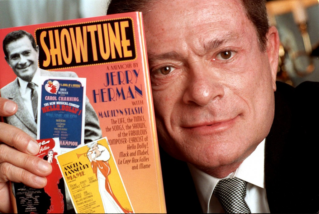"FILE - In this Nov. 19, 1996, file photo, composer Jerry Herman displays his book ""Showtune,"" in New York. Herman, the Tony Award-winning composer beh..."