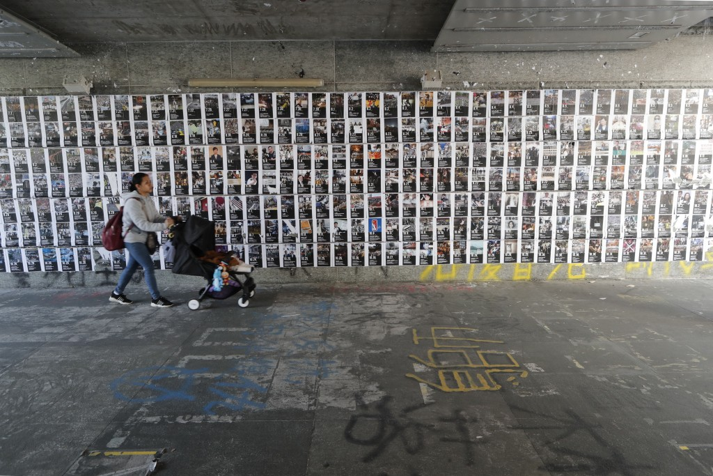 A woman pushes a baby carriage past a wall of posters featuring demonstration scenes in Hong Kong, Friday, Dec. 27, 2019. Hong Kong's demonstrations e...