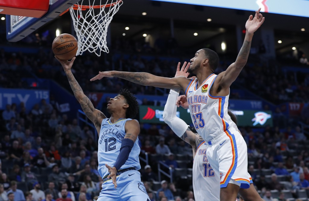 Memphis Grizzlies guard Ja Morant (12) goes to the basket as Oklahoma City Thunder guard Terrance Ferguson (23) defends during the second half of an N...
