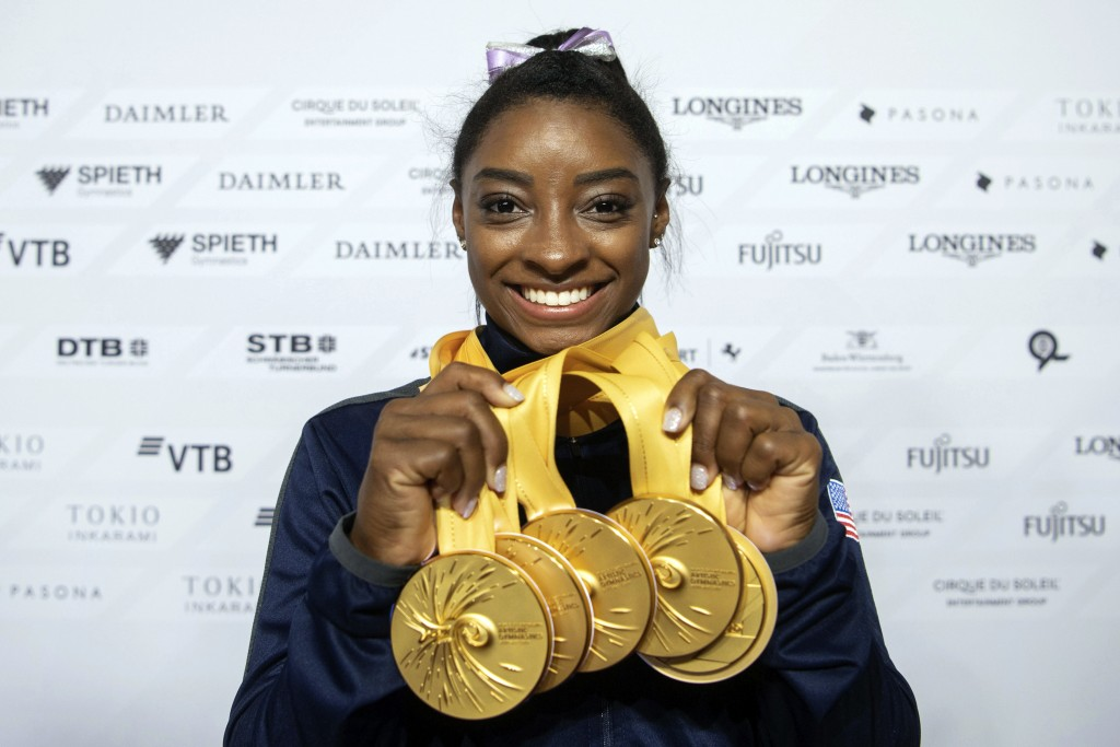 File-This Oct. 13, 2019, file photo Simone Biles of the United States shows her five gold medals at the Gymnastics World Championships in Stuttgart, G...