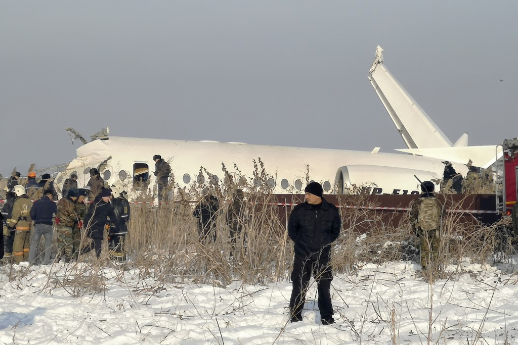 Police guard as rescuers work on the side of a plane crashed near Almaty International Airport, outside Almaty, Kazakhstan, Friday, Dec. 27, 2019. The...