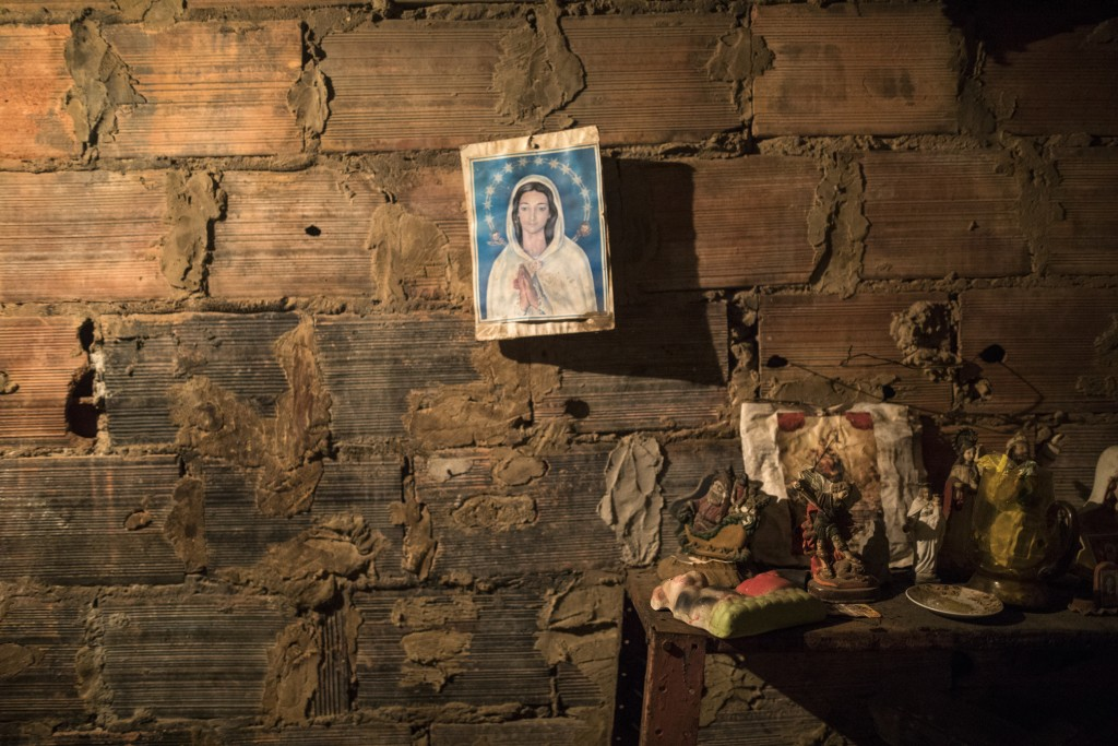 An image of the Virgin Mary hangs from a brick wall next to the room where the corpse of Teresa Jimenez is prepared following her death from natural c...