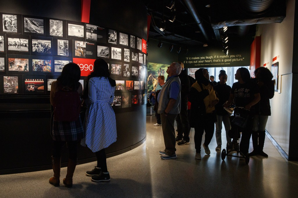 FILE - In this Friday, Dec. 20, 2019, photo, people visit the Pulitzer Prize Photography exhibition at the Newseum, in Washington. The Newseum will cl...