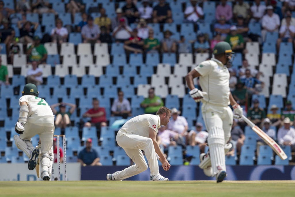 England's bowler Stuart Broad, middle, catches the ball to attempt a run-out against South Africa's batsman Anrich Nortje, left, on day two of the fir...