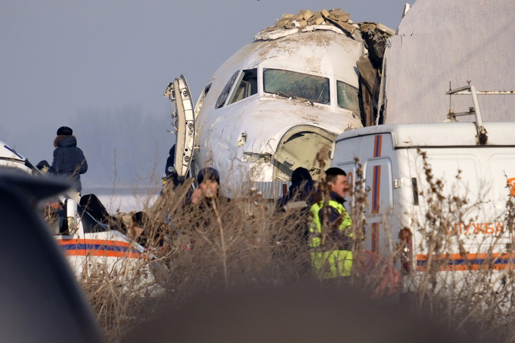 Police stand guard as rescuers assist on the site of a plane crashed near Almaty International Airport, outside Almaty, Kazakhstan, Friday, Dec. 27, 2...