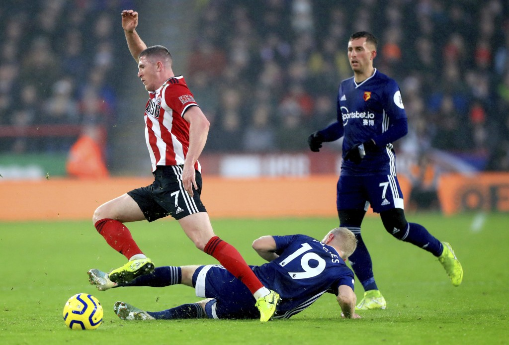Sheffield United's John Lundstram, left, and Watford's Will Hughes battle for the ball during their English Premier League soccer match at Bramall Lan...