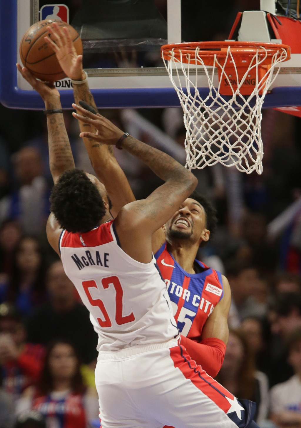 Detroit Pistons forward Christian Wood, right, defends against a shot by Washington Wizards guard Jordan McRae (52) during the first half of an NBA ba...