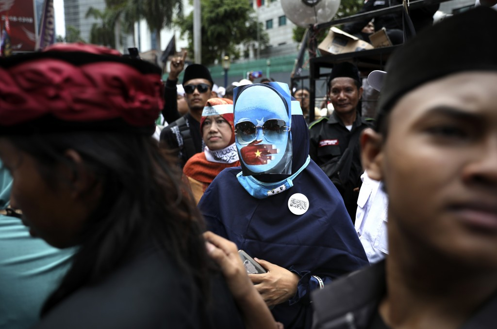 A Muslim woman wearing a pro-independence mask with the Eastern Turkistan flag attends a rally outside the Chinese Embassy in Jakarta, Indonesia, Frid...