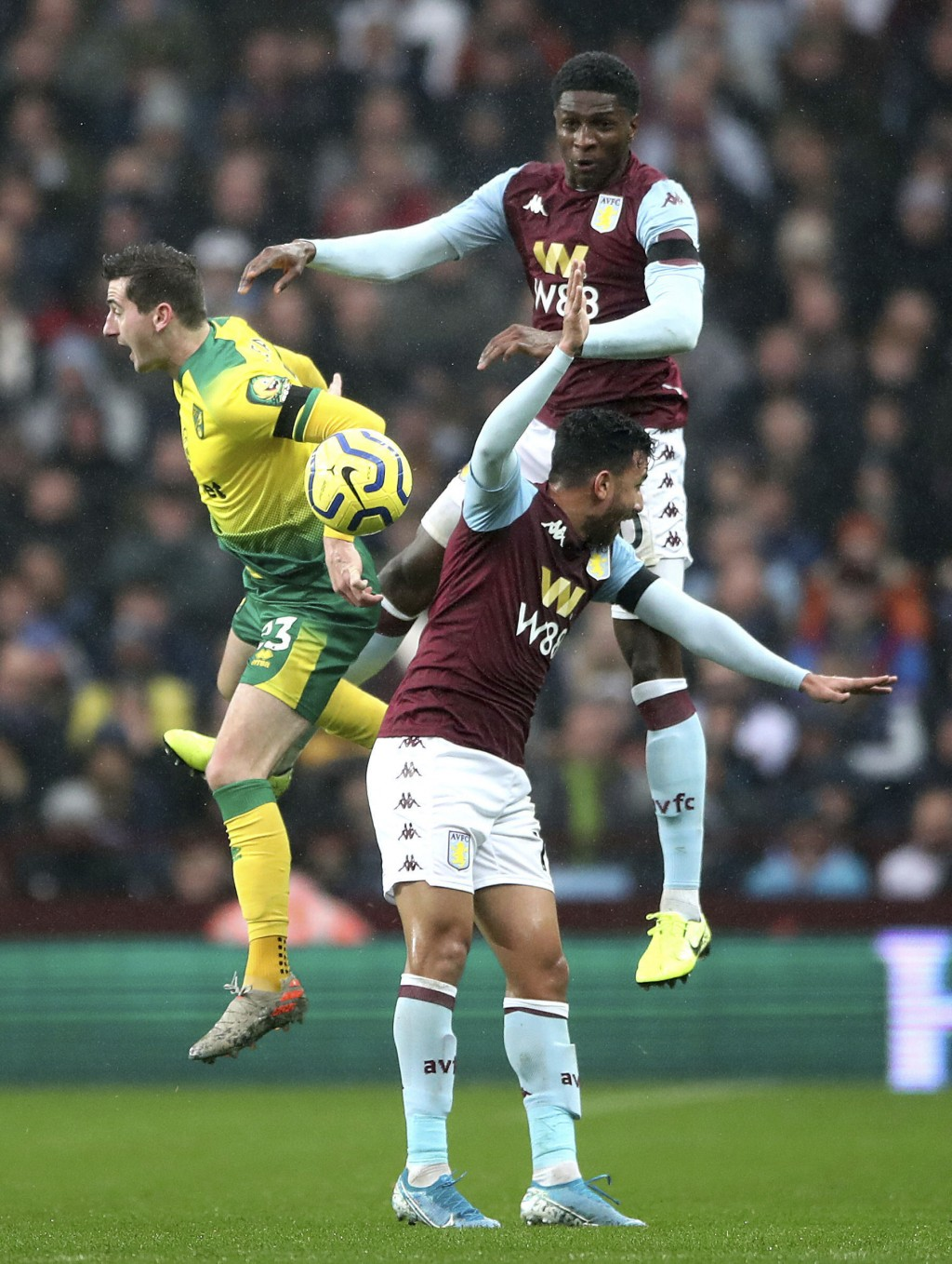 Norwich City's Kenny McLean, left, battles for the ball with Aston Villa's Kortney Hause, top, and Trezeguet during their English Premier League socce...