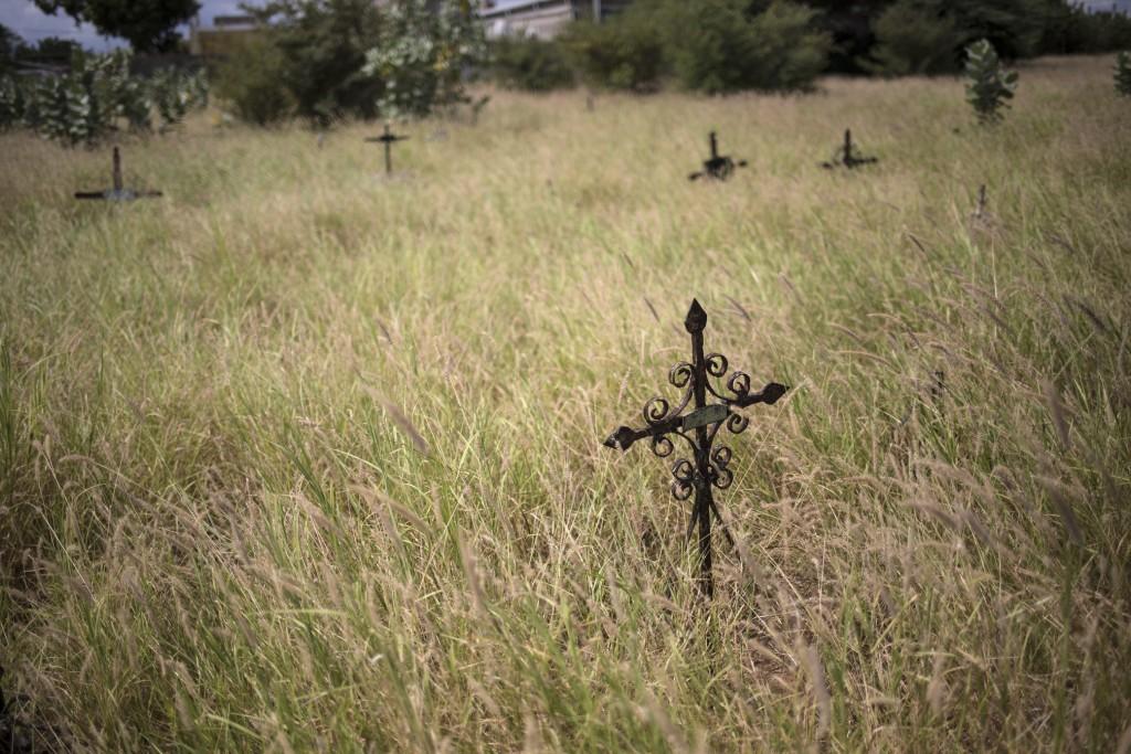 Crosses mark graves amid overgrown grass at Corazon de Jesus cemetery in Maracaibo, Venezuela, Nov. 21, 2019. Thieves often raid graves for valuables,...