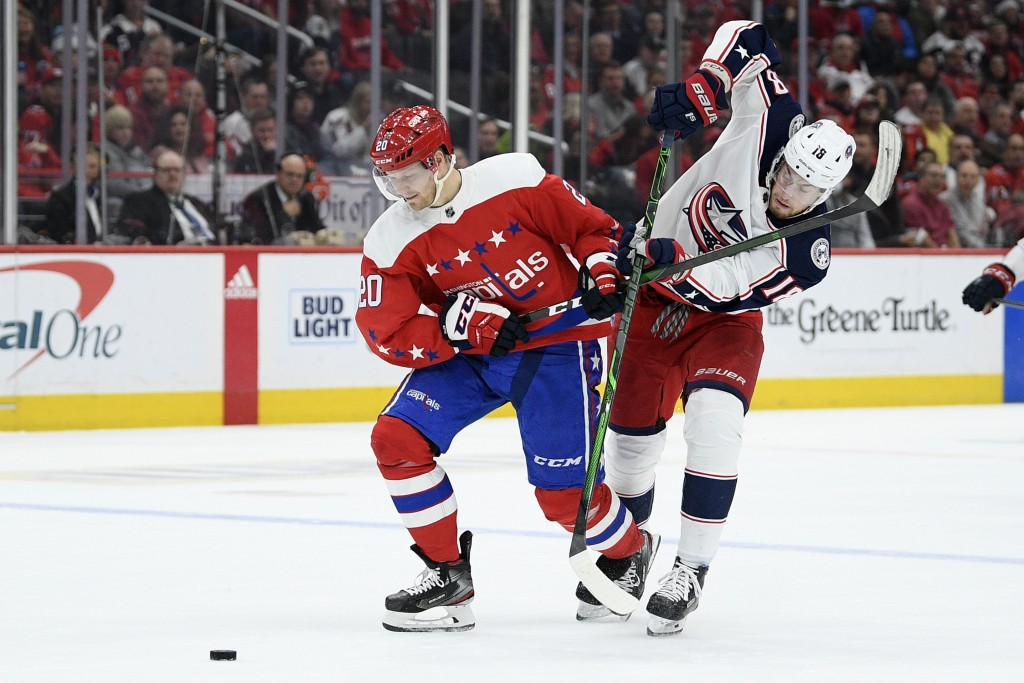Washington Capitals center Lars Eller (20), of Denmark, and Columbus Blue Jackets center Pierre-Luc Dubois (18) vie for the puck during the first peri...